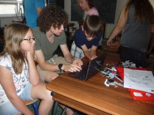 Žáci s instruktorem vytvářejí program Lego vozíku.